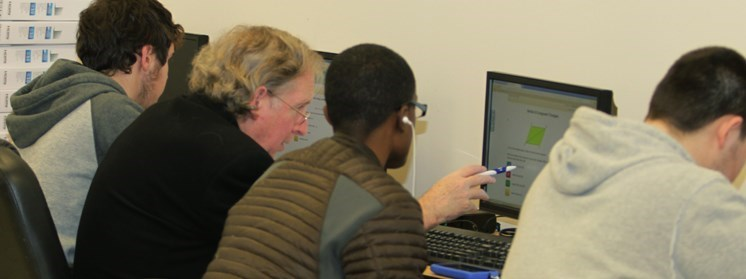 Teacher instructing student at a computer