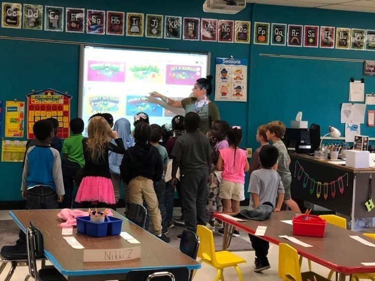 kids looking at the smartboard as the teacher explains what is on the screen