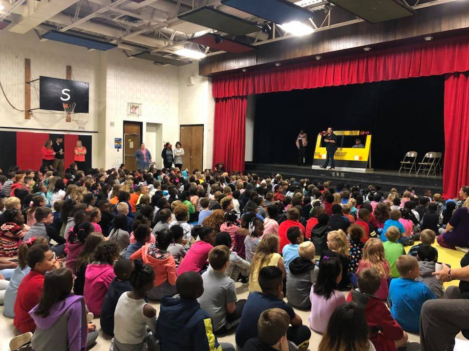 kids sitting in the gym listening to bus drivers talk about bus safety on stage