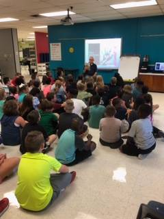 Students listen to Mr. Pease read a book
