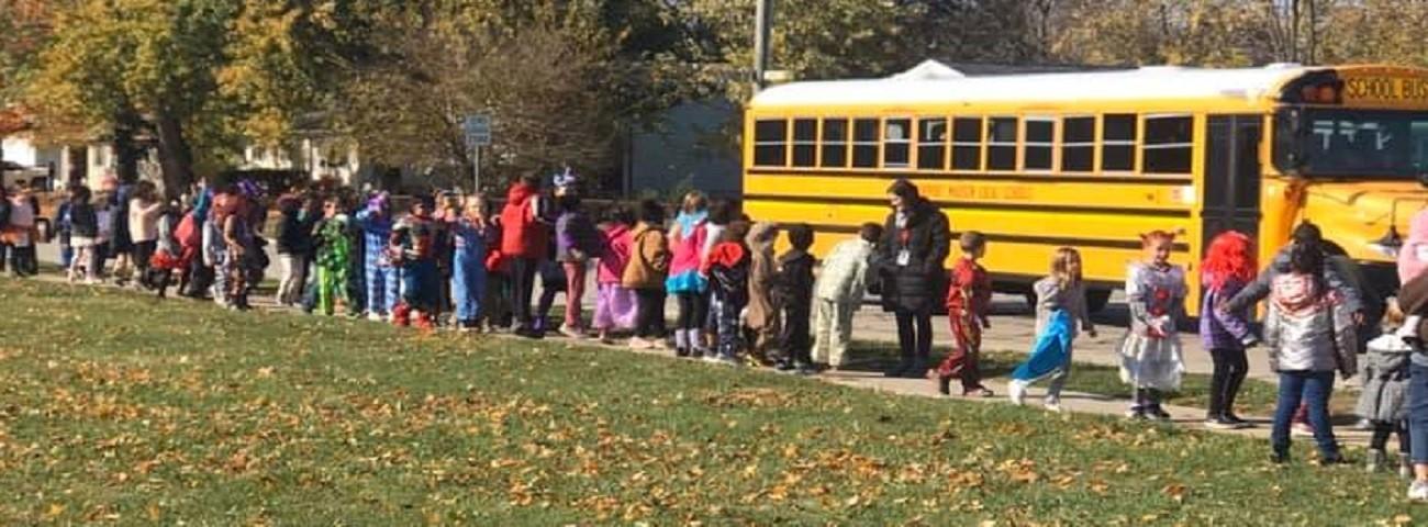 students walking down sidewalk in costumes
