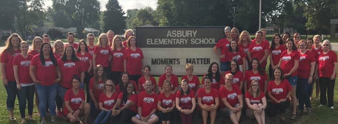 teachers in front of elementary school sign