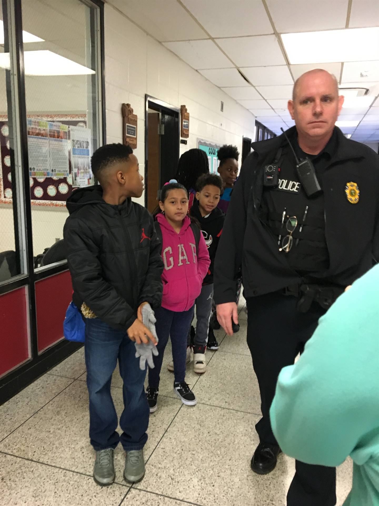 School Resource Officer Mallory greets students in the hall.