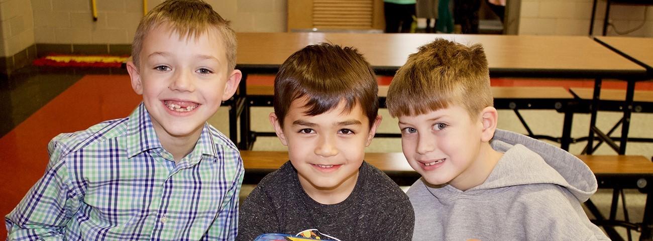 three boys eating lunch